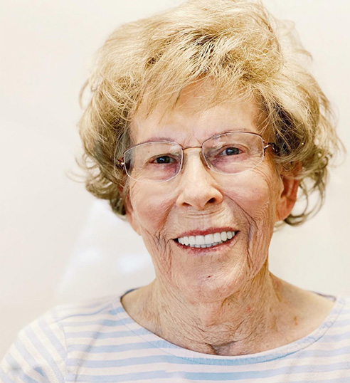 Older woman smiling with perfect teeth after all-on-4 procedure