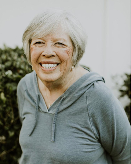 Older woman smiling with perfect teeth after all-on-4
